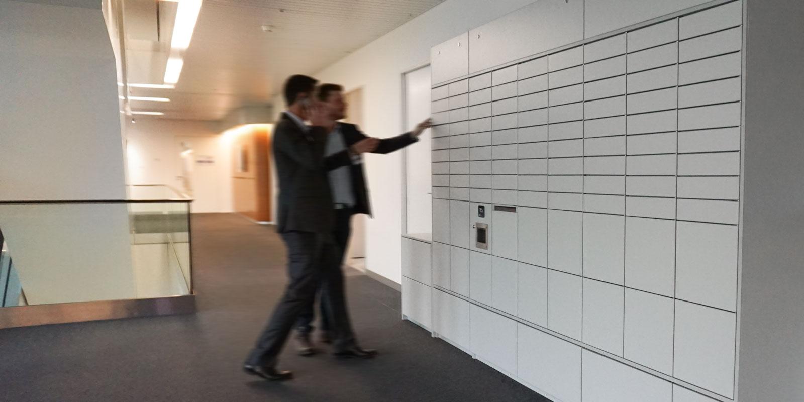 Personen öffnen ein Fach des Schranksystems NetLocker