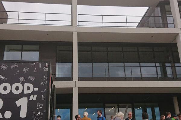 WordPress Teilnehmer stehen vor dem Unigebäude und genießen ihre Mittagspause